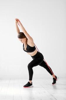 白いジムで全身の抵抗を行うパワーバンドで運動するアスリート女性がストレッチして筋肉を強化し、調子を整えます