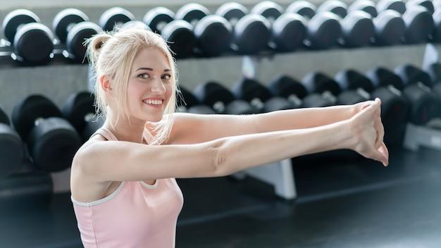 運動選手の女性は、コロナウイルスの発生時に自宅で運動します。強化する腕持久力トレーニング運動のための白人の女の子の運動。