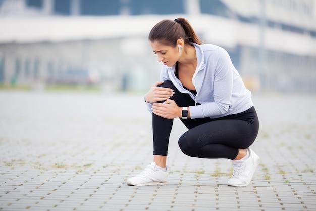 外傷を持っている膝を保持している運動選手の女性