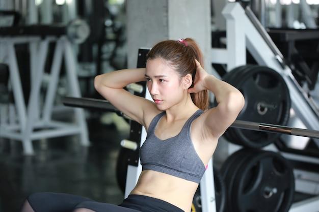 Атлетические женщины, выполняющие тренировку пресса в фитнес-зале
