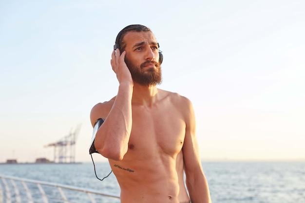 Atletico giovane ragazzo barbuto si riposa dopo lo sport estremo al mare, distoglie lo sguardo e ascolta le canzoni preferite in cuffia,