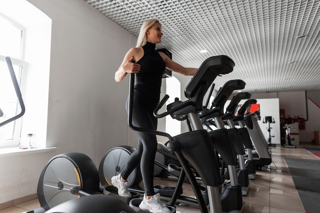 Спортивная молодая красивая женщина в черной футболке в стильных леггинсах в белых кроссовках тренируется на степпере