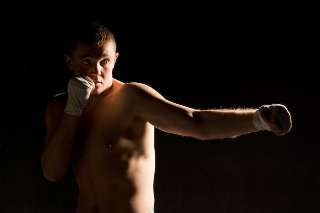 Athletic young boxer working out in the ring