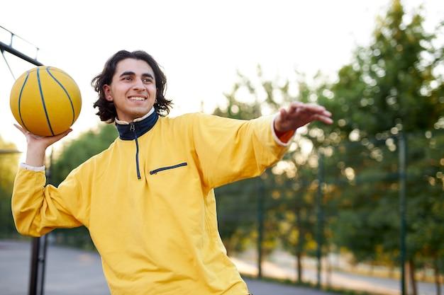 Спортивный молодой мальчик в повседневной одежде увлекается баскетболом