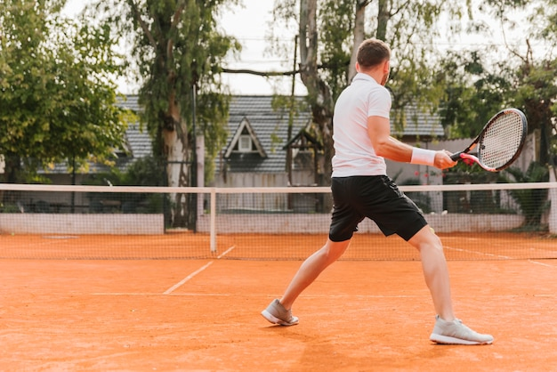Athletic young boy playing tennis