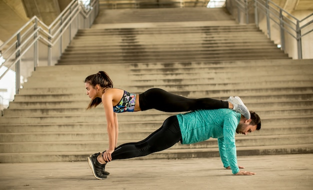 Athletic young couple doing stretching  exercises together