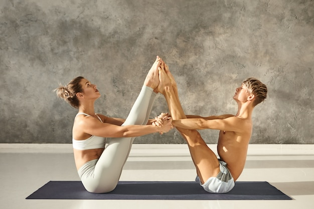 Athletic young couple practicing partner yoga at gym, sitting on one mat facing each other, bringing heels together and holding hands, doing navasana or boat pose. cooperation, trust and teamwork