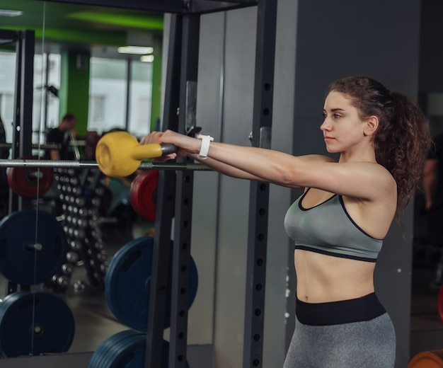 Athletic young fit woman doing exercise with kettlebell in the gym. free weights, functional training