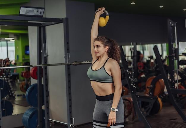 ジムでケトルベルで運動をしている運動の若いフィットの女性。フリーウェイト、ファンクショナルトレーニング