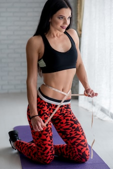 Athletic young girl measures her slender waist. healthy lifestyle.