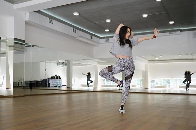 ストゥディで一人でスポーツとダンスを行う運動の若い女の子