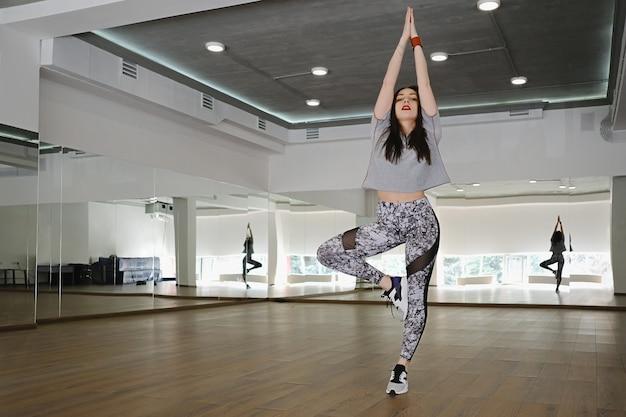 スポーツとダンスをスタジオで一人で実行する運動の若い女の子
