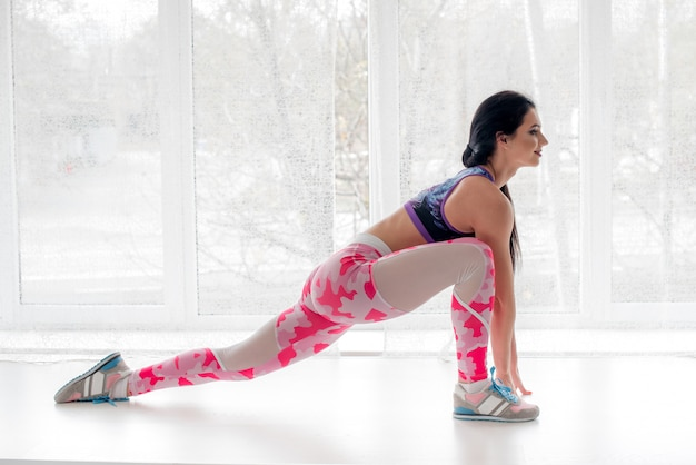 Athletic young girl performs exercises in the studio on a light background. fitness, healthy lifestyle