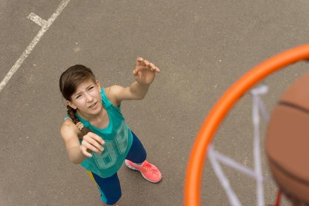 ボールがネットに入るときにバスケットボールでゴールを決める運動の若い女の子