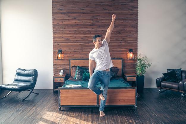 笑顔でスポーツ運動をしているベッドの近くに立っている裸足で運動の若い男。