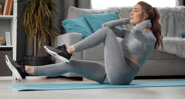 腹筋運動、腹筋運動、脚上げ、ひねりをして屋内にいる運動の若い女性