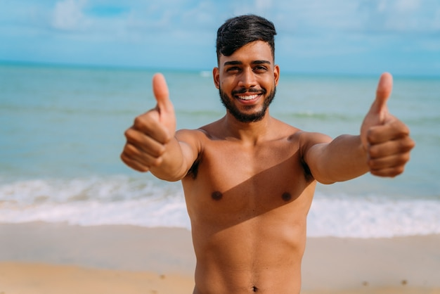 Athletic young latin american man on the beach with thumb up