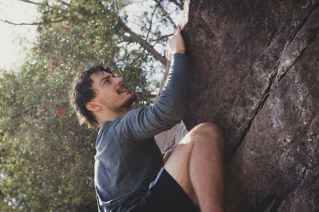 Athletic young man climbing rock mountain on sunny day outdoor workout exercise summer hiking
