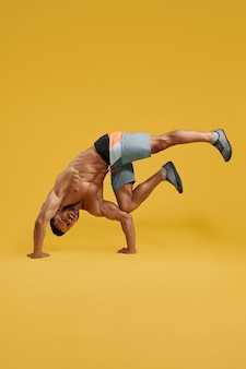 Athletic young man doing handstand exercise