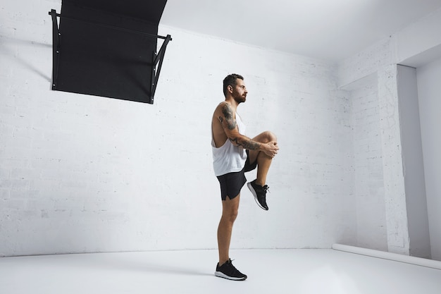 Спортивный молодой человек делает подъем коленей, вытягивает ноги, смотрит вправо, изолированный на белой кирпичной стене рядом со штангой