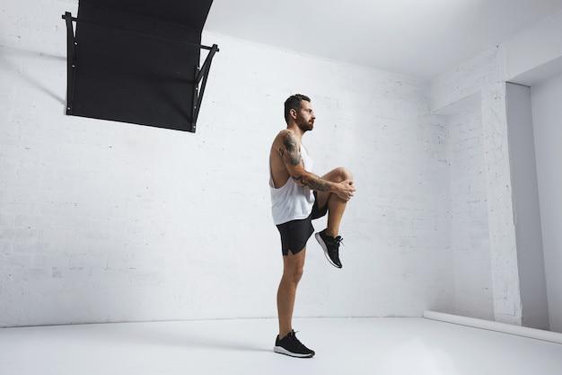 Giovane atletico che fa il ginocchio solleva, allungando le gambe, guardando a destra, isolato sul muro di mattoni bianchi accanto alla barra di trazione
