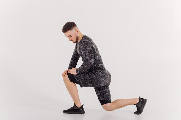 Спортивный (ый) молодой человек делает тренировки дома, человек делает тренировку, разогревается перед упражнениями с отягощениями.