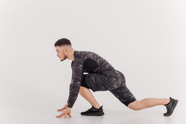 自宅でトレーニングをしている運動の若い男性、トレーニングをしている男性、体重運動の前にウォームアップします。