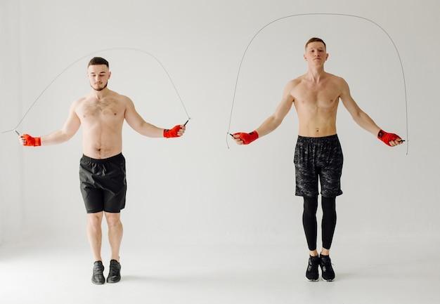 Giovane atletico che fa gli allenamenti a casa, uomo che fa formazione, riscaldamento prima dell'esercizio con i pesi.
