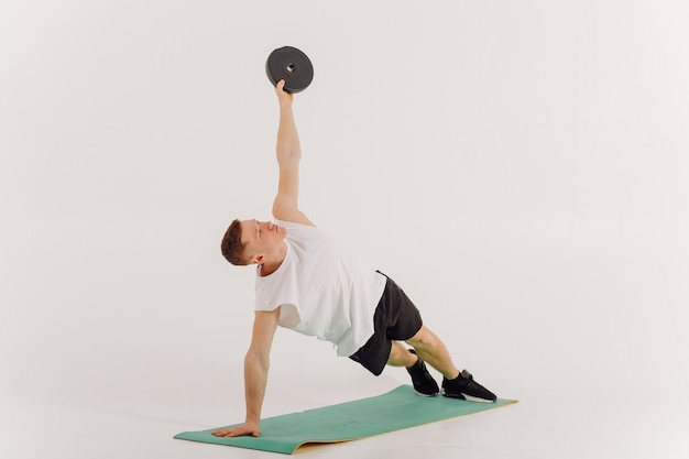 Athletic young man doing workouts at home, man doing training, warm up before weight exercise.