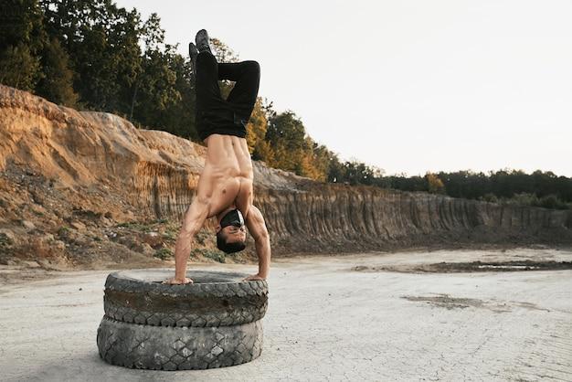 屋外でのトレーニング中に手に立っている間足を持ち上げて運動の若い男。砂場でのトレーニングに重いタイヤを使用しているフェイスマスクの上半身裸の男。