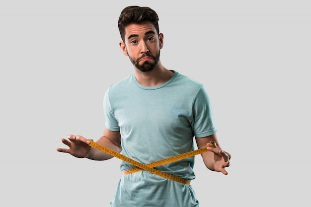 Athletic young man holding tape measure