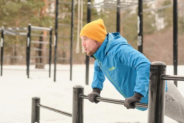 冬のトレーニンググラウンドでバーから腕立て伏せをしている黄色い帽子と手袋の運動青年