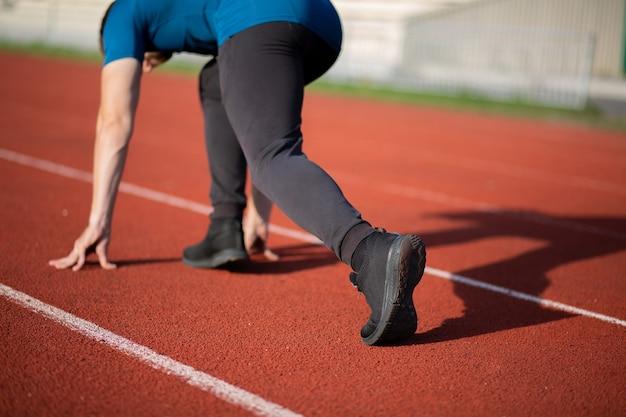 빨간 달리기 트랙에서 달릴 준비가 된 운동 청년. 뒷모습. 근접 촬영