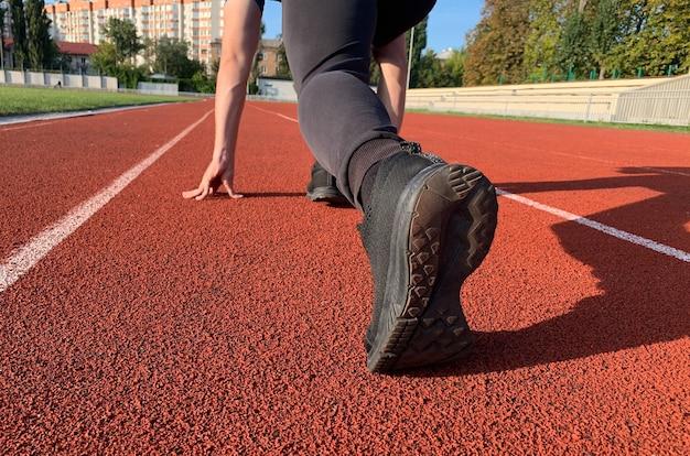 빨간 달리기 트랙에서 달릴 준비가 된 운동 청년. 근접 촬영