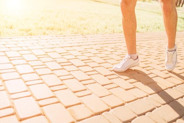 自然の中を走っている運動青年。健康的な生活様式。ひげを生やした黒髪のスポーツマンが道路を走っています-日没のバックライトが点灯しています。