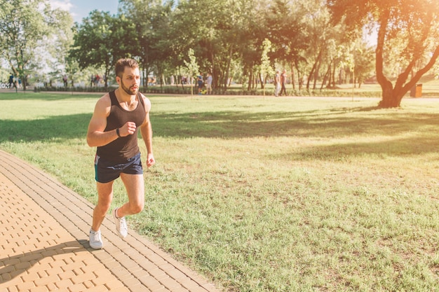 自然の中で実行している運動の若い男。健康的な生活様式。ひげを生やした黒い髪のスポーツマンは道路で実行されている-日没のバックライト