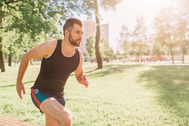 自然の中で走っている運動の若い男。健康的な生活様式。ひげを生やした黒い髪のスポーツマンが道路で実行されている-日没のバックライト