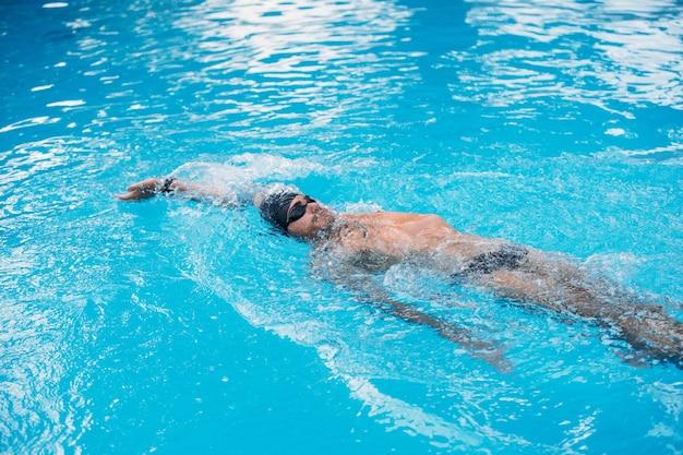 背泳ぎスタイルで泳ぐ運動青年。水泳大会。