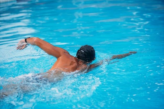 プールでクロールを泳いでいる運動の若い男。水泳大会。