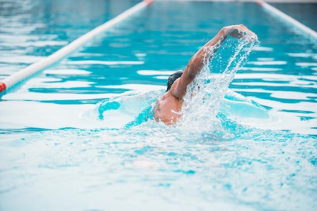 Спортивная (ый) молодой человек, плавание спиной ползать в бассейне.