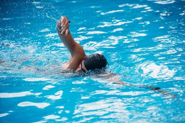 Спортивная (ый) молодой человек плавание переднего обхода в бассейне. соревнования по плаванию.