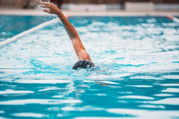 Спортивная (ый) молодой человек плавание переднего обхода в бассейне.