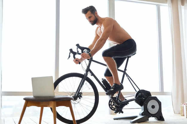 집에서 자전거 트레이너를 사용하는 운동 청년