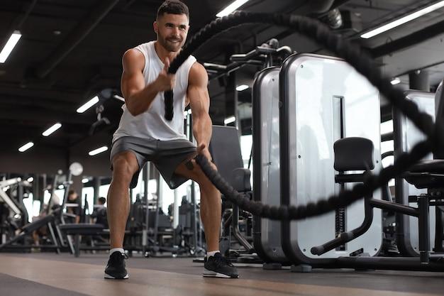 ファンクショナルトレーニングフィットネスジムで運動をしているバトルロープを持つ運動青年。