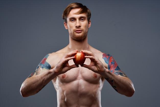 筋肉の筋肉と腹筋の裸の胴体リンゴの健康を持つ運動の若い男