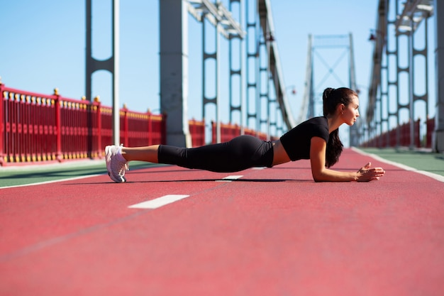Athletic young model doing plank exercise outdoor at the bridge in sunny morning