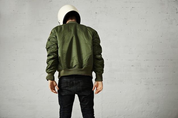 Спортивная молодая модель в узких джинсах, зеленой куртке-бомбардировщике и белом мотоциклетном шлеме, изолированном на белом, портрет сзади