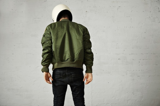 Athletic young model in skinny jeans, green bomber jacket and white motorcycle helmet isolated on white, back portrait