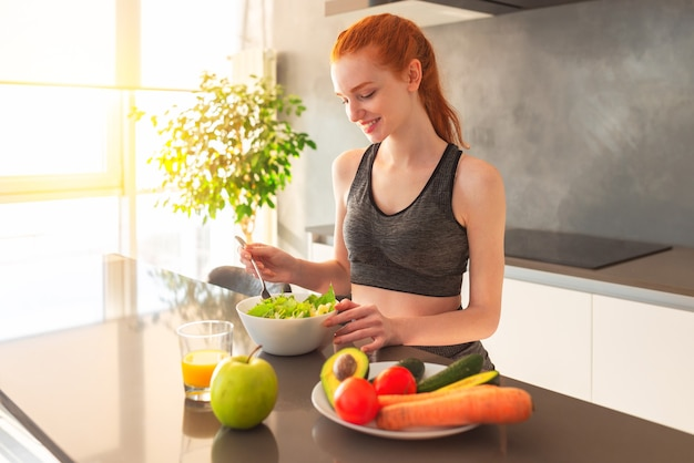 Athletic young red haired woman in the home kitchen eating a healthy salad