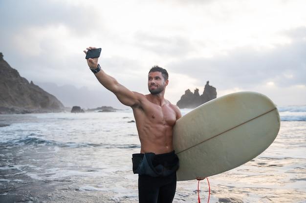 Спортивный молодой серфер делает селфи на пляже, спортивный парень держит доску для серфинга и стоит на тропическом пляже во время заката - спортивный миллениал, использующий технологии и практикующий экстремальные виды спорта.